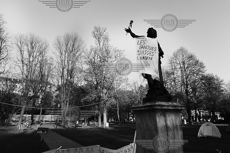 A slogan on a statue in the Parc des Bastions by the encampment of 'les indignes', the Occupy movement, reading 'Les Banques Suisses l'argent.'