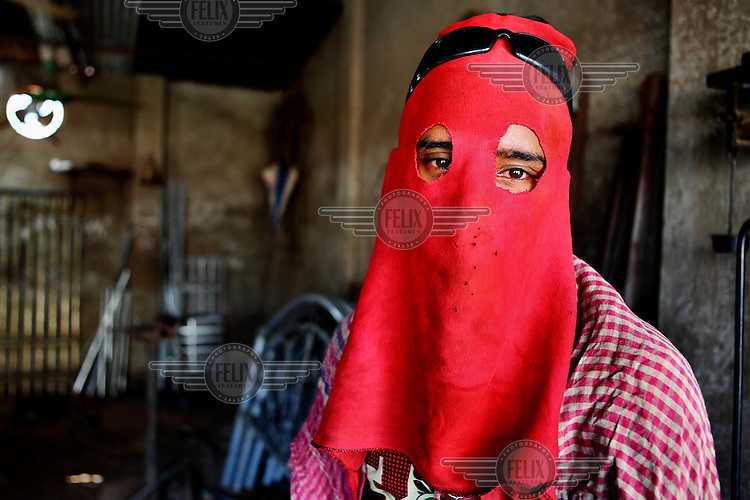 Rony (25) made his own 'safety mask' for his job in an electric welding shop. A risky occupation, where workers are always scared of being injured by the flame. Rony works from 8am to 8pm and manages to earn 3,500 Taka per month to support his family. This mask made of cloth will not protect him from an accident - however, it is still a consolation as it takes away some of the fear.