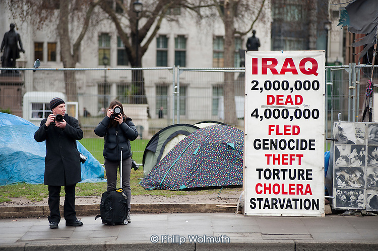 Two tourists take photographs in front of the peace camp and anti-war placard in Parliament Square.
