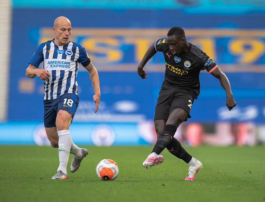 Manchester City's Benjamin Mendy (right) under pressure from Brighton & Hove Albion's Aaron Mooy (left) <br /> <br /> Photographer David Horton/CameraSport<br /> <br /> The Premier League - Brighton & Hove Albion v Manchester City - Saturday 11th July 2020 - The Amex Stadium - Brighton<br /> <br /> World Copyright © 2020 CameraSport. All rights reserved. 43 Linden Ave. Countesthorpe. Leicester. England. LE8 5PG - Tel: +44 (0) 116 277 4147 - admin@camerasport.com - www.camerasport.com