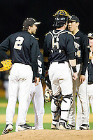Wake Forest Demon Deacons relief pitcher Max Tishman (34) gets instructions from catcher Brett Armour (6) and third baseman Mark Rhine (2) during the game against the West Virginia Mountaineers at Wake Forest Baseball Park on February 24, 2013 in Winston-Salem, North Carolina.  The Demon Deacons defeated the Mountaineers 11-3.  (Brian Westerholt/Four Seam Images)