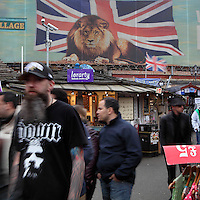 "Open air areas with stalls and customers, Candem Town markets, open-air and indoor markets, London, UK. The wall poster showing a lion with the Union Jack is the emblematic picture of ""Camden World Famous Market"". Picture by Manuel Cohen"