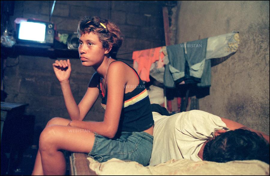 2000. Daily life of street kids in Managua, Nicaragua. Mercedes, a 14-years old gang member, on the bed of her 50-years old boyfriend. Mercedes un membre du gang de 14 ans, sur le lit de son petit ami de 50 ans.