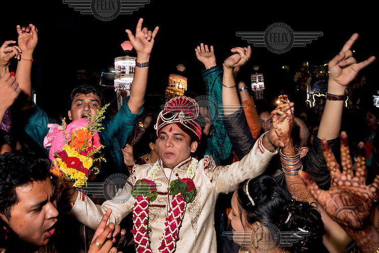 The groom and his party dance in the streets of Navsari on the way to his marriage ceremony.