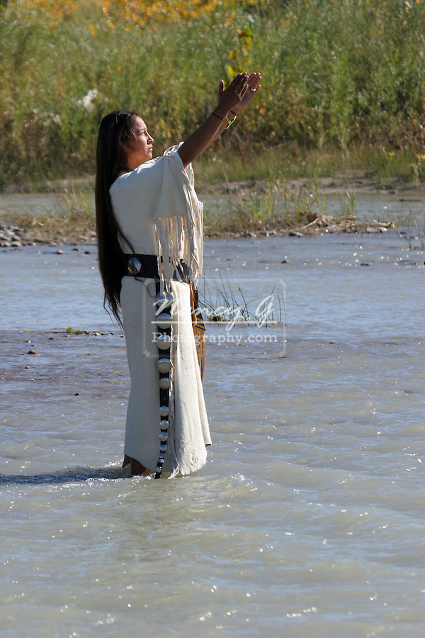 An Native American Indian women standing in the river holding her arms up to the sun