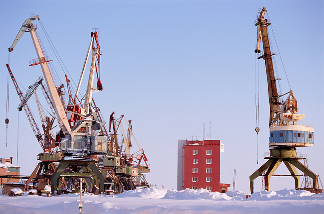 Cranes in Dudinka docks during the winter time. Taymyr, Northern Siberia, Russia.