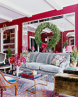 The walls of the sitting room are sheathed in a bold red felt and a mirrored panel on the wall gives a sense of space to the room. The custom-made sofa is upholstered in a blue Lee Jofa velvet and the cocktail table is 1960.