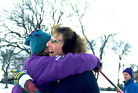 Friends age 45 hugging at end of Lake Phalen cross country ski race.  St Paul  Minnesota USA