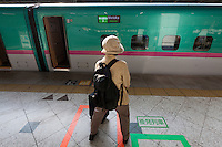 A older Japanese woman waits for a new, Hayabusa, Super Express Bullet Train at Ueno Station, Tokyo, Japan. Friday May 10th 2013