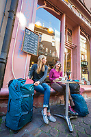 Two women traveling in Colmar, France, exploring the colorful old city, stopped outside a cafe.