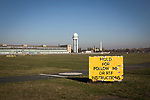 A tower and hangars situated behind a sign on the former runway at the disused Tempelhof airport in Berlin, Germany. The historic airfield was constructed in 1923, used by the Nazis for rallies and became the site of the American airlift during the blockade of West Berlin  by the USSR. In October 2015, giant hangars were converted into temporary accommodation space for hundreds of refugees arriving in Berlin.