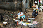 Street market woman selling raw  fish besides an open sewer. Three streets away from the Strand Hotel. Yangon Myanmar ( Rangoon Burma ) South East asia 2006.