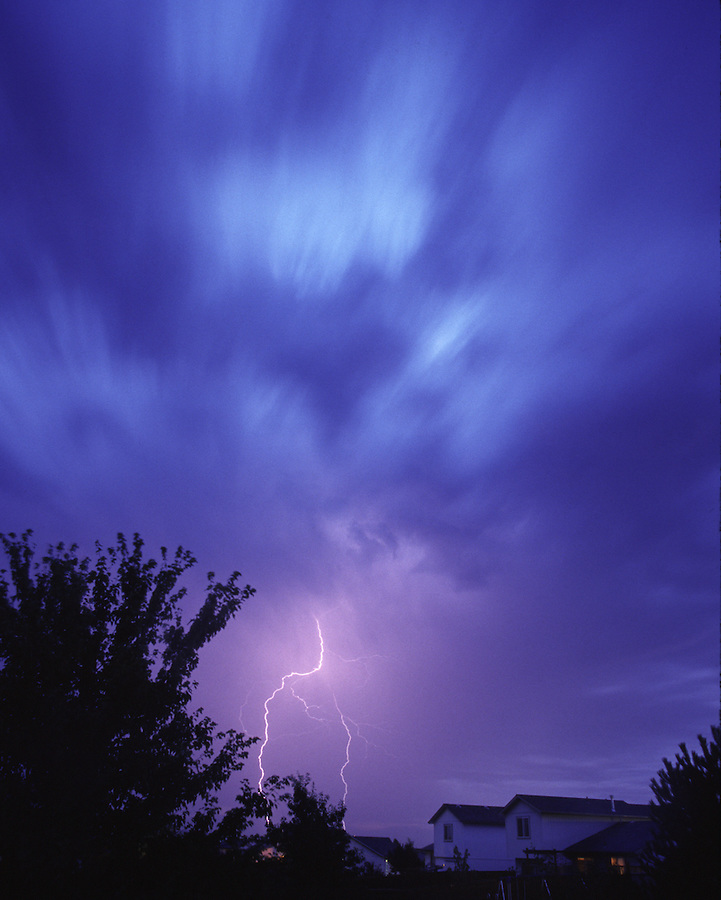 The clouds streak by in a time exposure as lightning strikes near a home in a suburban development.