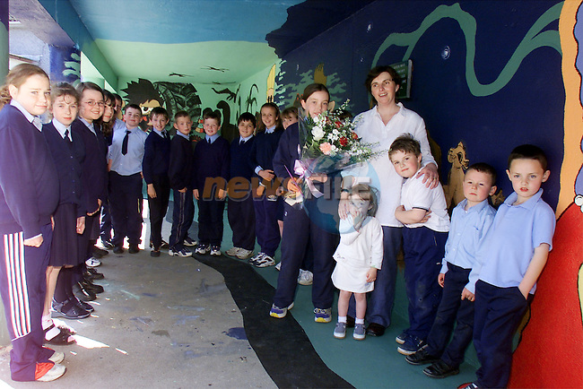 Pupils of Dunleer NS present Rosemary Martin with a bunch of flowers as thanks for the time she put into painting their school's mural...Picture: Arthur Carron/Newsfile