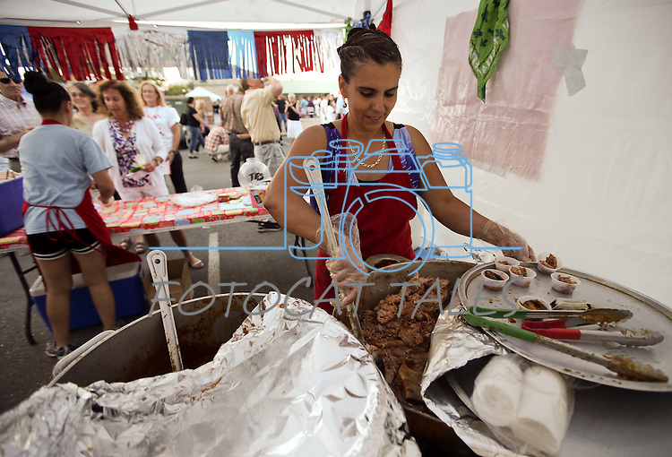 Fidelina Suarez, owner of The Lady Tamales, cooks at the 20th annual Taste of Downtown event in Carson City, Nev., on Saturday, June 15, 2013. The event features 44 local restaurants in a fundraiser for the Advocates to End Domestic Violence.<br /> Photo by Cathleen Allison