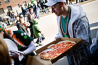 A man holds a pizza on the sidewalk during the St. Patricks' Day Parade in South Boston, Massachusetts.