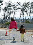 March 11, 2013, Sendai, Japan - A mother and her child visit where their home once was near a beach by the Pacific Ocean in Sendai, Miyagi Prefecture, on Monday, March 11, 2013, as the nation observes the second anniversary of the March 11, 2011 disaster.  (Photo by Natsuki Sakai/AFLO)