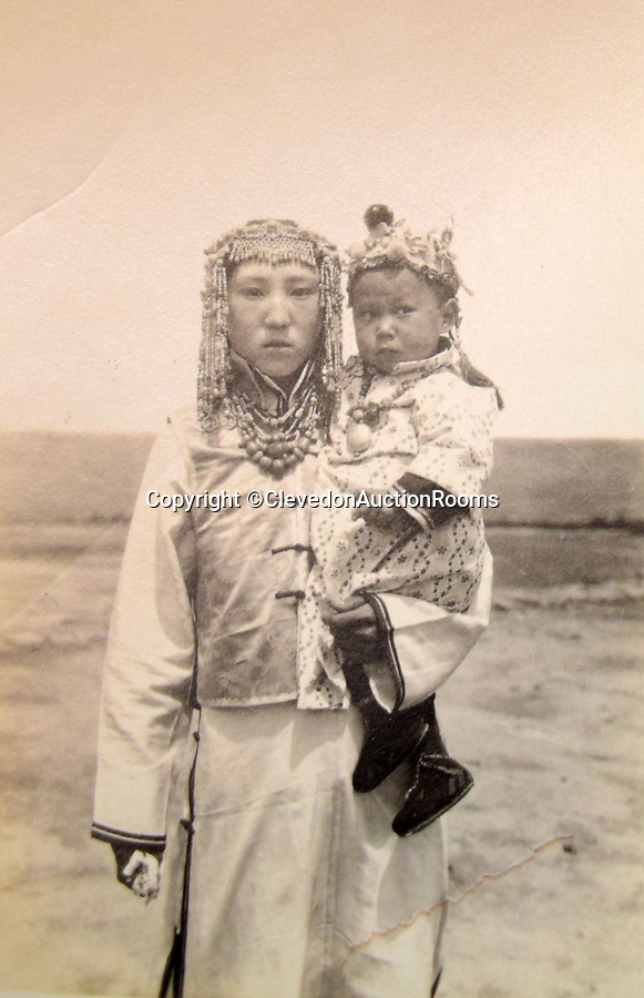 BNPS.co.uk (01202 558833)<br /> Pic: ClevedonAuctionRooms/BNPS<br /> <br /> Nomadic Mongol women and child..<br /> <br /> Rev Francis John Griffith travelled as a Missionary aroud Outer Mongolia in the 1920's.<br /> <br /> A fascinating collection of early 20th century photos of Mongolia and China which were taken by a British vicar doing missionary work have been unearthed after 97 years.<br /> <br /> Through his famine relief work Reverend Francis John Griffith was able to get a remarkable insight into the lives of the native population and their nomadic existence.<br /> <br /> His encounters were captured using a handheld camera that he carried with him at all times.<br /> <br /> In one image a family goes about its business outside the hut that is their home, while another image is of a man riding a camel which was the typical method of transport.<br /> <br /> Revd Griffith was able to get native elders to sit for him in portraits and there are intimate snaps of women and children wearing elaborate native headdresses.<br /> <br /> As well as the people, Revd Griffith took an interest in the surroundings and photographed temples and prominent buildings in addition to the vast, desert landscape.