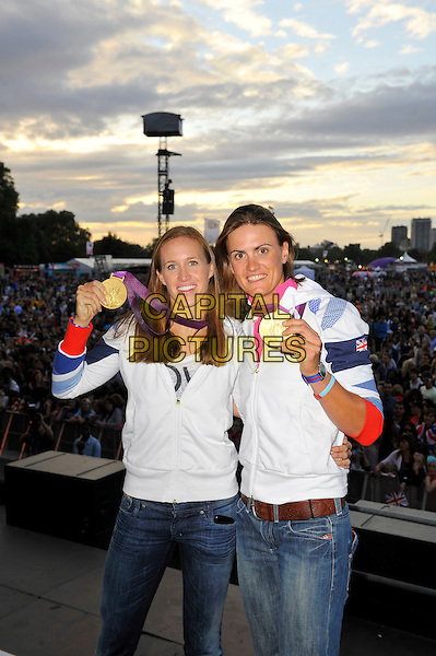 Helen Glover and Heather Stanning, Olympic Gold Medal Winners for Team GB, attending BT London Live, Hyde Park, London, England..2nd August 2012.stage half length white jacket jeans denim winners rowing rowers.CAP/MAR.© Martin Harris/Capital Pictures.