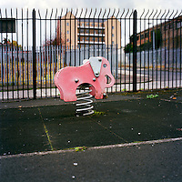 A plastic pink elephant on a large spring used by children as a rocking horse stands in front of the 'interface wall' that divides Protestant and Catholic communities in.Alexandra Park, North Belfast.