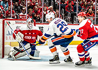 WASHINGTON, DC - JANUARY 31: The puck flies past the head of Braden Holtby #70 of the Washington Capitals during a game between New York Islanders and Washington Capitals at Capital One Arena on January 31, 2020 in Washington, DC.