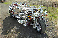 BNPS.co.uk (01202 558833)<br /> Pic: EssexClassicCarAuction/BNPS<br /> <br /> A unique three wheeled 'Mad Max' style monster bike is sure to get bidders revved up when it goes under the hammer.<br /> <br /> The road legal Jike Trike - part bike, part car - is the only specimen of its kind in the world and is valued at &pound;30,000.<br /> <br /> The original owner invested &pound;50,000 and dedicated more than 4,000 hours to making his vision of a car-bike hybrid come true with jaw-dropping results.<br /> <br /> The 18 ft trike, which has a front and two backseats, was created from the body of a 1992 Jaguar XJS. <br /> <br /> It is powered by a 12 cylinder 5.3 litre V12 Jaguar XJS engine which is on display for all to see and in theory could do 150 mph.  <br /> <br /> The Jaguar's back end was lifted to create the back end of the trike and its wide Chip Foose wheels, which are needed to support its massive frame, were imported from the USA.