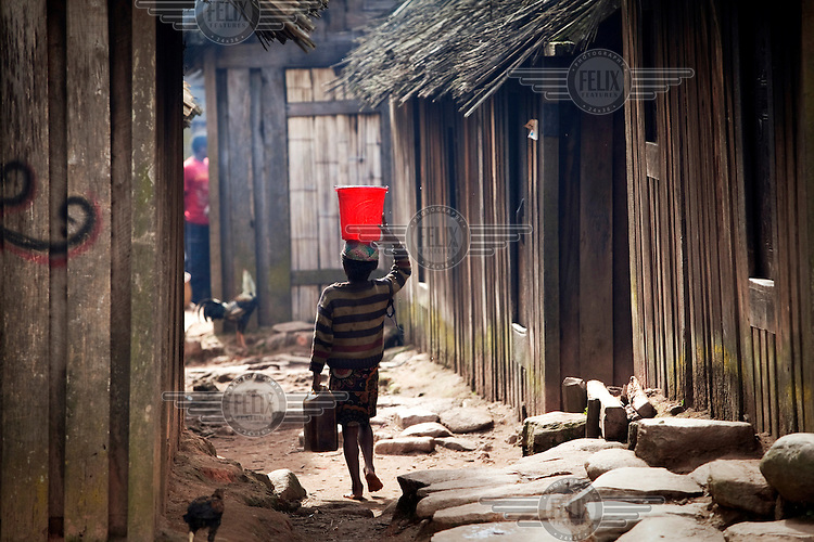 A girl carries a bucket of water on her head along an alleyway in the village of Zafimaniry.
