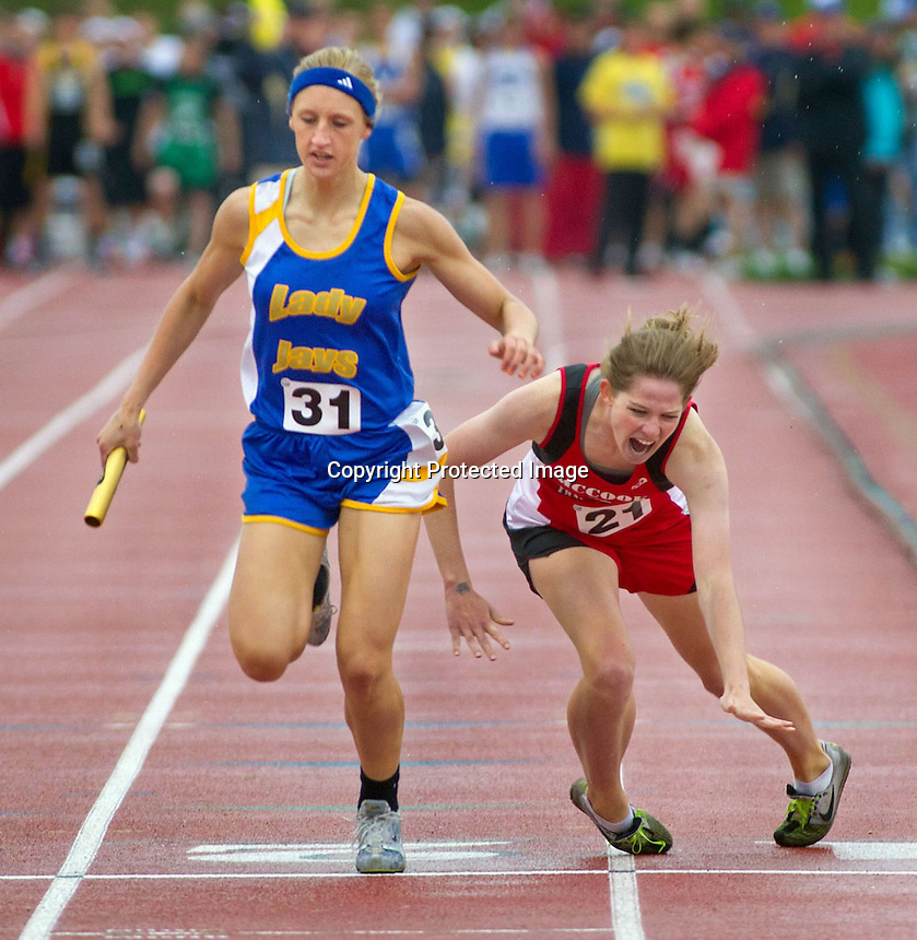 Seward's Hannah Tvrdy breaks the state record in the girls class B 3200-meter relay as McCook's Jessa Sughroue, falls at the finish line. Record Tumbles Photo by Kent Sievers/Omaha World-Herald