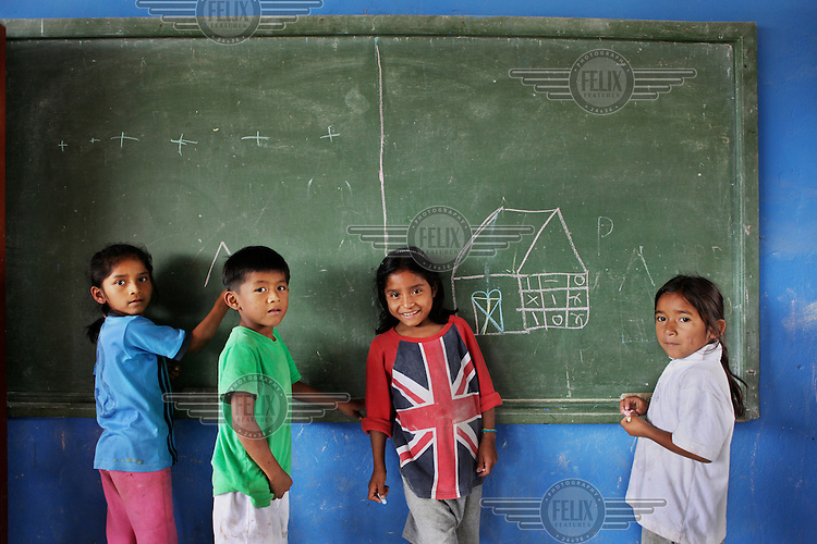 Children write on a blackboard in a school in the Oriente. This is the Amazon rainforest region of eastern Ecuador, it is inhabited by a tiny fraction of the country's population. Most of the people living here are indigenous people and illiteracy is widespread.