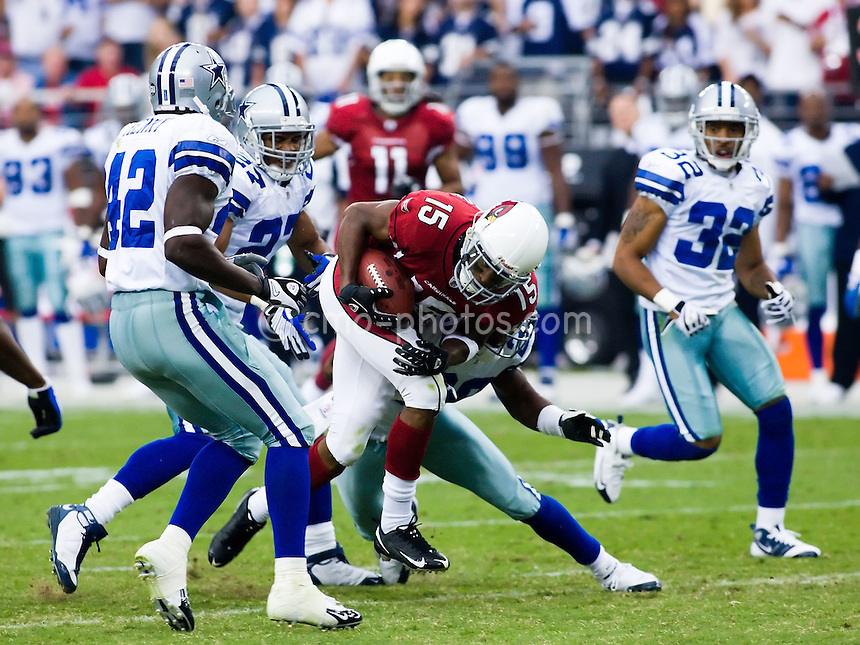 Oct 12, 2008; Glendale, AZ, USA; Arizona Cardinals wide receiver Steve Breaston (15) is tackled by a Dallas Cowboys defender while Dallas Cowboys cornerback Anthony Henry (42), Dallas Cowboys safety Courtney Brown (27), and Dallas Cowboys cornerback Orlando Scandrick (32) chase down the play in the third quarter of a game at University of Phoenix Stadium.  The Cardinals won the game in overtime 30-24.