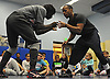 Coaches Nikken Fauntleroy, right, and Quindell Ross show grappling techniques to their wrestlers during practice at Copiague High School on Tuesday, Jan. 31, 2017.