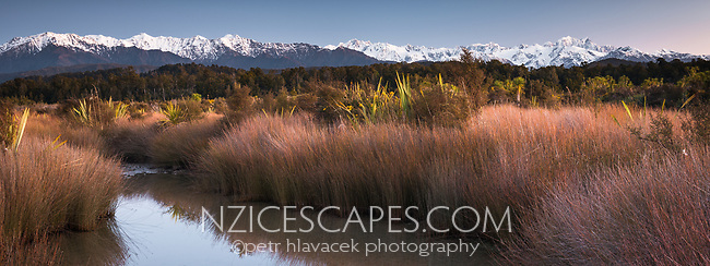 Pastel colours of twilight over Southern Alps with Aoraki Mt. Cook and Mt. Tasman from Okarito Lagoon, Westland Tai Poutini National Park, West Coast, UNESCO World Heritage Area, South Westland, New Zealand, NZ