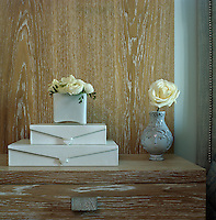 A small vase filled with flowers on a pile of white leather boxes on a limed wood side table