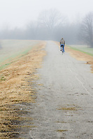 A lone cyclist on the bike trail along the Arkansas River in Fort Smith Arkansas, on a foggy fall morning.