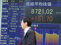 June 18, 2012, Tokyo, Japan - A businessman walks past the stock market board showing the figure for the Nikkei 225 in downtown Tokyo. The Nikkei 225 climbed 151.70 points to 8,721.02 at Tokyo's 3pm closing. Greece's positive election vote helped ease fears that the country may fall out from the euro currency. (Photo by Christopher Jue/AFLO)