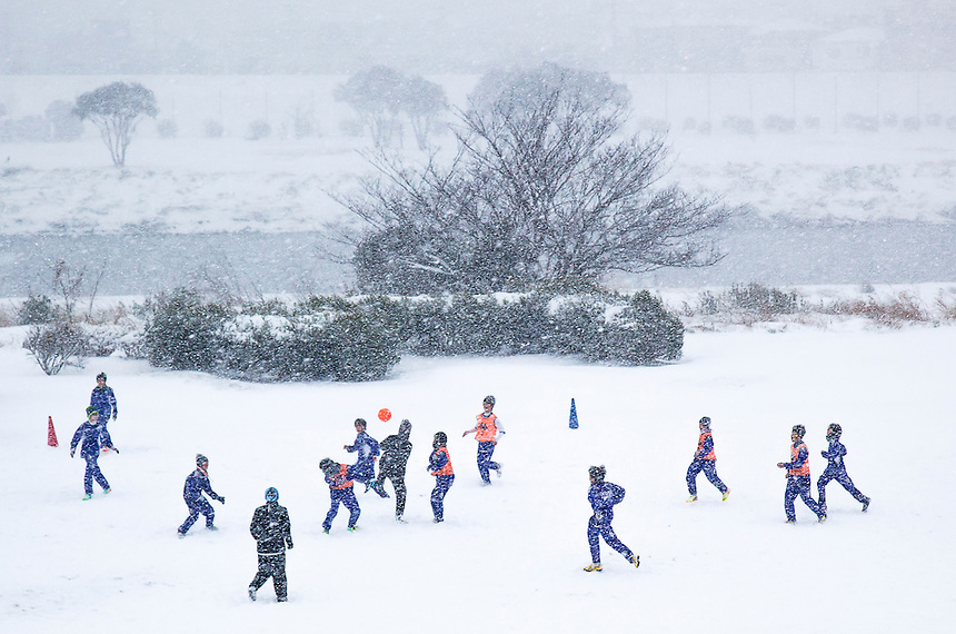 Youths playing football in Tokyo`s heaviest snow in 46 years.