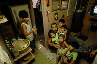 Ramina Jardo at home with some of her 7 children and her father Roy Deguzman in the tiny apartment typical slum area of Manila where families commonly have between 6- 12 children. There is no family planning available from the Government due to a law passed by the Mayor and they are too poor to pay for their own contraception.