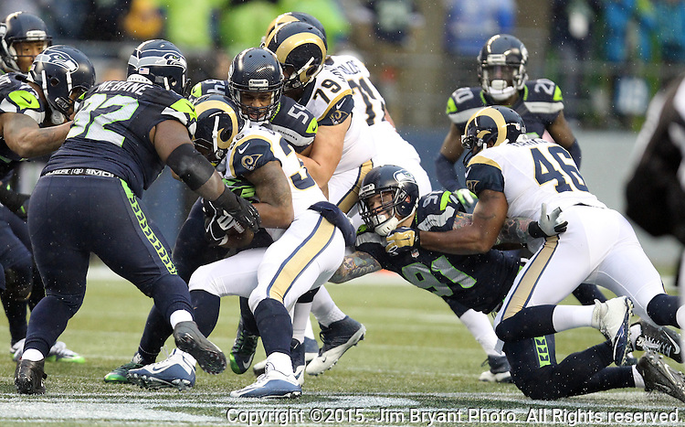 Seattle Seahawks defenses, Cassius Marsh (91), Brandon Mebane (92) and Bobby Wagner (54) team up to tackle St. Louis Rams running back Benny Cunningham (36) at CenturyLink Field in Seattle, Washington on December 27, 2015.  The Rams beat the Seahawks 23-17.      ©2015. Jim Bryant Photo. All Rights Reserved