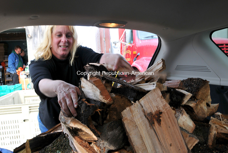ENW HARTFORD, CT 31 OCTOBER 2011--103111JS02---Kateri Pilon of Canton loads fire wood into the back of her vehicle after purchasing a half bin at Gresczyk Farms in New Hartford on Monday. Pilon said she was out of poweer and was going to use the wood in her fireplace. <br /> Jim Shannon Republican-American