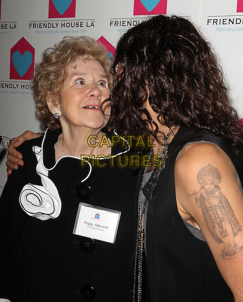 Peggy Albrecht & Russell Brand.Friendly House LA Annual Awards Luncheon Held At The Beverly Hilton Hotel, Beverly Hills, California, USA..October 27th, 2012.half length black grey gray top sleeveless beard facial hair tattoo side profile brown necklaces .CAP/ADM/KB.©Kevan Brooks/AdMedia/Capital Pictures.