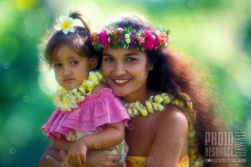 Close-up of a beautiful Polynesian woman with her daughter, in colorful aloha wear and wearing plumeria and huku leis. Set against a background of muted green foliage.