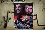 A poster of Hezbollah leader Sheik Hassan Nasrallah and Medhi Army leader Moqtada al-Sadr hangs on a wall in the Baghdad Shiite neighborhood of Shula on Saturday August 19, 2006.