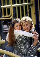 A smiling young girl and her mother play on playground equipment.