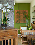 Cushions on carved wooden seat in green living room