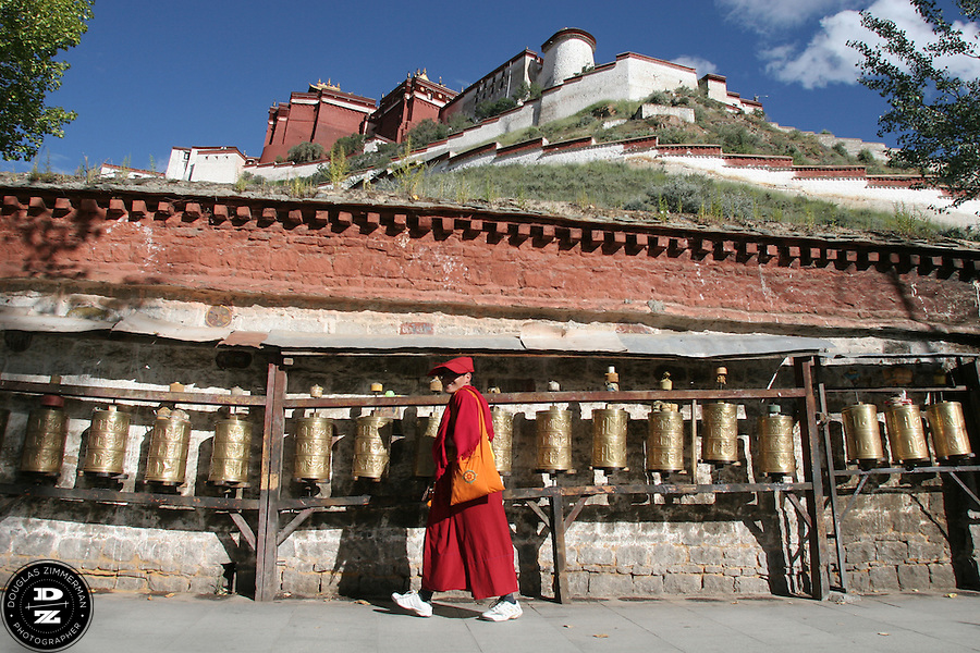 A Buddhist monk turns a prayer wheel while  walking a kora (pilgrimage circuit) around the Potala Palace in Lhasa, Tibet. The Potala Palace is the former residence of the Dalai Lama and is considered a revered religious structure in Tibet.  Photograph by Douglas ZImmerman
