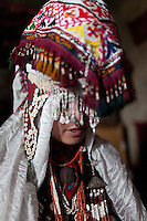 A woman tries on her Kyrgyz wedding outfit..In and around the camp of Ortobil, Manara (Sufi camp), near the borders with China and Tajikistan...Trekking with yak caravan through the Little Pamir where the Afghan Kyrgyz community live all year, on the borders of China, Tajikistan and Pakistan.