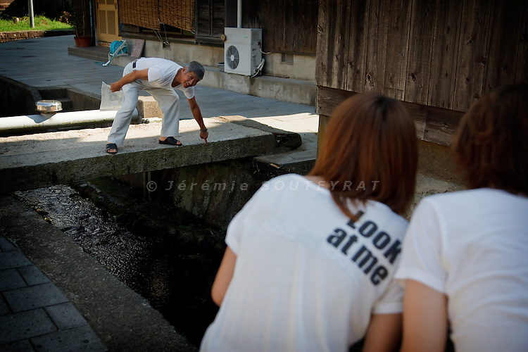 Sado island, August 19 2010 - Shukunegi, small harbour near Ogi city. The village prospered from ship building and shipping business during the Edo period (17th to 19th centuries). A local showing to two young tourists the Edo dating inscription on the stone bridge.