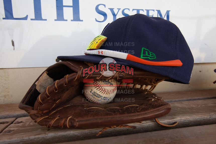 A Midwest League baseball sits in a glove below a Cedar Rapids Kernels hat during a game against the Lansing Lugnuts at Veterans Memorial Stadium on April 30, 2013 in Cedar Rapids, Iowa. (Brace Hemmelgarn/Four Seam Images)