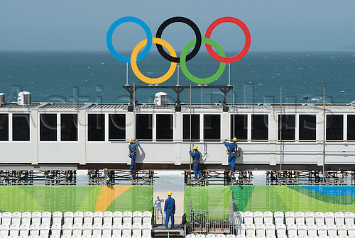 02.08.2016. Rio de Janeiro, Brazil.  Construction workers operating underneath the Olympic Rings in the beach volleyball arena at Copacabana beach prior to the Rio 2016 Olympic Games in Rio de Janeiro, Brazil, 2 August 2016. Rio 2016 Olympic Games take place from 05 to 21 August.