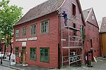 Foto: VidiPhoto..BERGEN - In het Noorse Bergen is de restauratie van de Bryggen -de handelshuizen uit de 13e eeuw- een constant proces. De kleurrijk geschilderde Hanzehuizen, gebouwd door Duitse kooplieden, zijn de grootste toeristische trekpleister van de op één na grootste stad van Noorwegen. De tientallen houten huizen in de wijk zijn vooral in gebruik bij kunstenaars en winkeliers. Met name een drietal aannemers houdt zich op dit moment bezig met onderhoud en restauratie van de panden. De gemeente Bergen houdt dat nauwlettend in de gaten. Het gebied is opgenomen op de Werelderfgoedlijst van UNESCO.